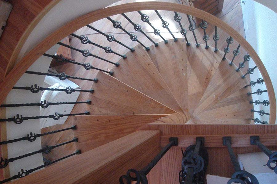 Cầu thang xoắn bằng gỗ có lan can bằng kim loại và họa tiết xinh xắn.