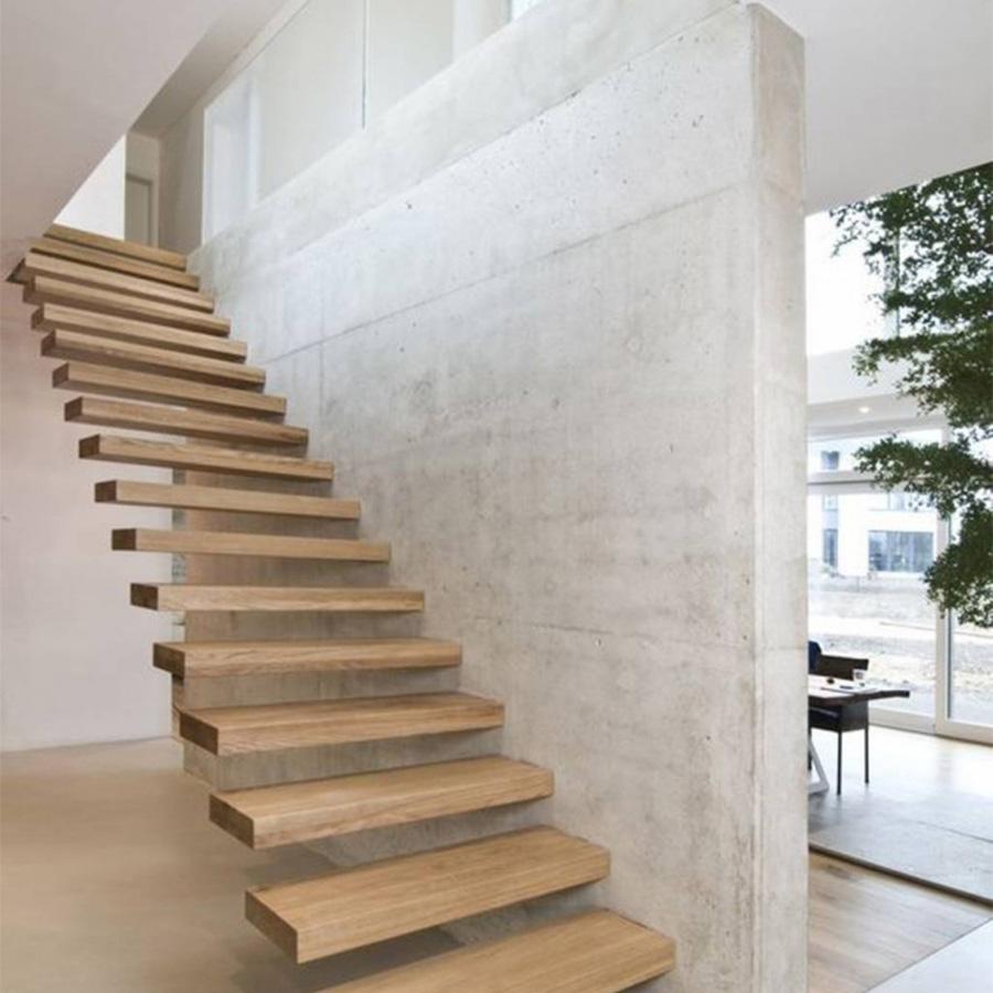 Mẫu cầu thang xương cá sử dụng chất liệu gỗ với phần khung sống ẩn bên trong tường bê tông, phần lan can được tối giản hoàn toàn.